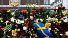 A Swedish flag and flowers are left at a makeshift memorial near the site where a truck drove into a crowd   on Friday, in central Stockholm. Photograph: Jonathan Nackstrand/AFP/Getty Images