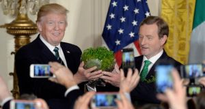 US president Donald Trump accepts a bowl of shamrock from Taoiseach Enda Kenny at the White House in Washington, DC, on March 16th. Photograph: Olivier Douliery/EPA