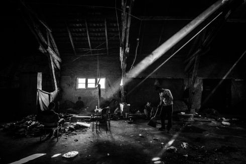 A man sweeping the floor inside a warehouse which has become a temporary home for about 1,000 refugees and migrants in Belgrade, Serbia. Despite the conditions in which they subsist, they try to keep the place in good condition. All photographs : Szymon Barylski