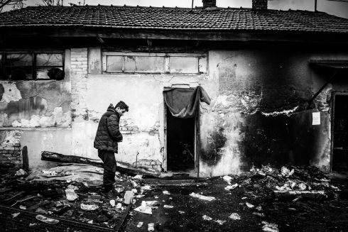 Man at the front of abandoned building, which is his temporary shelter, at the back the main train station Serbia, Belgrade.  In spring 2016 the Balkan route to western Europe was officially closed, so refugees are stranded in Belgrade.