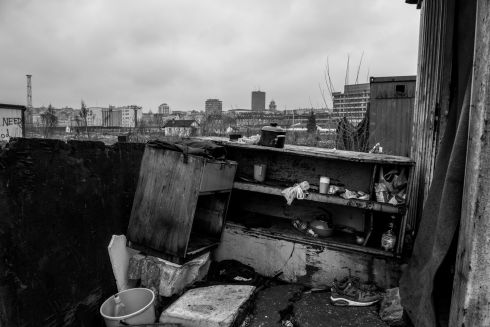 In the foreground, a makeshift outside kitchen in temporary shelter, and in the background Belgrade developing city.