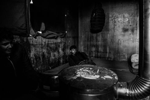 A man warms himself by the stove in temporary shelter at the back main train station in Belgrade, Serbia.