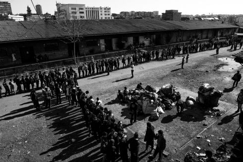General view on the makeshift shelter where around 1,000 refugee living. Men queue for lunch provided by volunteers at the barracks Serbia, Belgrade.