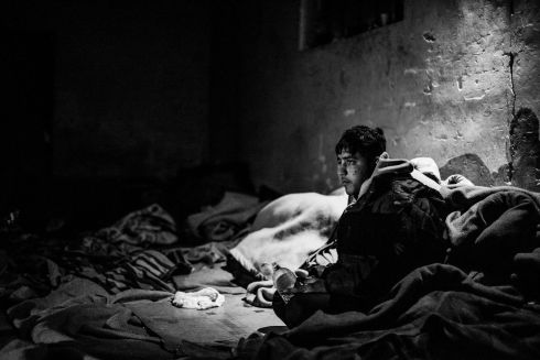 Stranded refugee inside derelict warehouse where people have to use blanket to warm themselves.