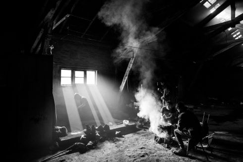 Men gather around a fire at the barracks.  Photo story by Szymon Barylski - see the full story by Dan McLaughlin at this link - http://www.irishtimes.com/news/world/europe/life-in-a-warehouse-serbia-s-stranded-migrants-and-refugees-1.3040900