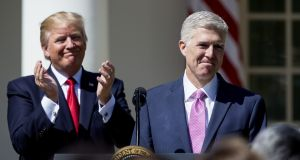 Newly sworn-in US supreme court justice  Neil Gorsuch speaks as President Donald Trump looks on during a ceremony in the Rose Garden at the White House on Monday. Photograph: Eric Thayer/Getty Images