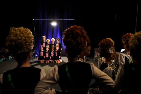 Dancers look on backstage as a performing group have their photo taken before performing during the World Irish Dancing Championships in Dublin. Photograph: Clodagh Kilcoyne