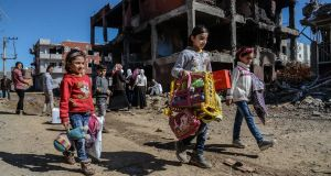 Young girls walk next to ruined houses and shops in Cizre on  international women's day last year. The buildings were destroyed in an operation by Turkish authorities against Kurdish opponents. Photograph: Ilyas Akengin/AFP/Getty