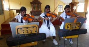 Mallavi Central College students Kaleirasi, L Sharaniya and Nishanthini during a Music Project violin lesson. Photograph: Joseph O'Connor