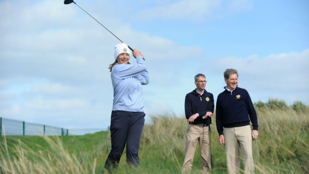 Andrea Fitzgerald, lady captain of the Castle Golf Club, Dublin, tees off watched on by Eamonn Duggan, chairman, and Barry McConville, captain, during the Allianz/The Irish Times Officers Challenge golf tournament in Portmarnock Hotel and Golf Links Dublin. Photograph: Aidan Crawley