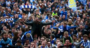 Brighton & Hove Albion fans celebrate on the pitch after their team's victory against Wigan Athletic at Amex Stadium. Photograph: Dan Istitene/Getty Images
