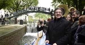 Communist-backed candidate Jean-Luc Mélenchon campaigns in the French presidential election on  a barge  on the Canal Saint-Martin  in Paris on Monday. Photograph: Alain Jocard/Reuters