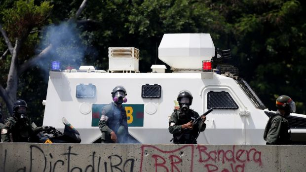 Riot police take position during the march. Photograph: Carlos Garcia Rawlins/Reuters