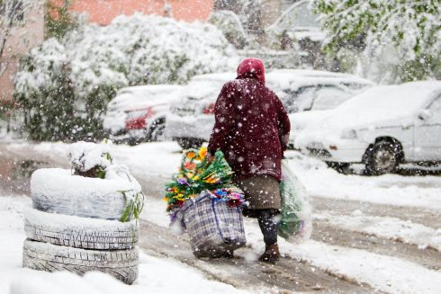COLD SNAP: An elderly woman carries bags containing artificial flowers during snowfall in downtown Chișinău, Moldova. Photograph: Dumitru Doru/EPA
