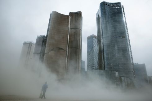 COLLECT DUST: A man walks through a cloud of dust whipped up by wind at a construction site, in Beijing, China. Photograph: Thomas Peter/Reuters