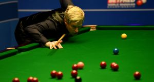 Neil Robertson lines up a shot against Noppon Saengkham during their first round match of the World Snooker Championship at the Crucible Theatre  in Sheffield. Photograph: Gareth Copley/Getty Images