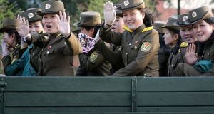 North Korean soldiers wave from the back of a truck at oncoming traffic on Thursday. Photograph: AP