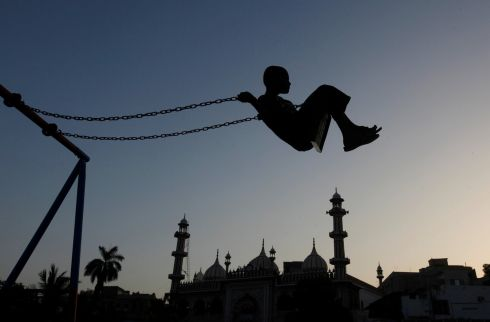 FLYING HIGH: A boy plays on a swing during sunset hours near a mosque in Karachi, Pakistan. Photograph: Akhtar Soomro/Reuters