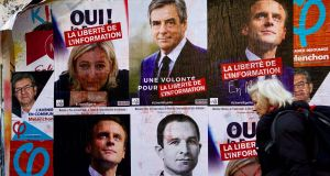 A woman walks past electoral posters of French presidential election candidates in Paris. Photograph: Gabriel Bouysgabriel Bouys/AFP/Getty Images