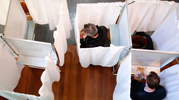 Voters pick their candidates inside voting booths at a polling station in Paris on Sunday. Photograph: Benjamin Cremel/AFP/Getty Images