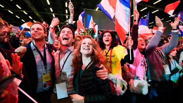 Supporters of Emmanuel Macron French presidential election candidate for the En Marche! movement celebrate after the results of the first round of the presidential election at the Parc des Expositions in Paris