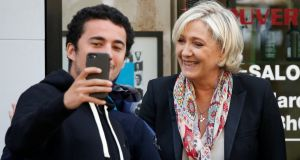 Marine Le Pen poses for a selfie as she leaves the hair dresser in front of her campaign headquarters in Paris on Monday. Photograph: Reuters
