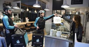 Bikers working for food-delivery service Deliveroo enter a restaurant to pick up meals they will deliver in Paris. Photograph:  Eric Feferberg/AFP/Getty Images