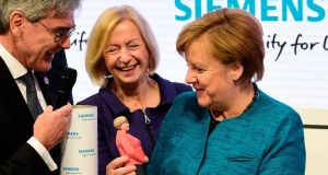 German chancellor Angela Merkel holds a 3D printed figurine of herself at the Hannover Messe trade fair. Photograph: Tobias Schwarz/AFP