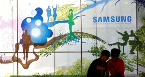 Children look at a mobile phone in front of an advertisement of Samsung Electronic at its store in Seoul, South Korea.