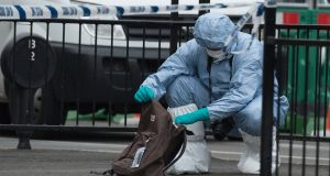 A forensic officer examines items left on the footpath after police arrested a man following an incident in London, England. Photograph: Will Oliver/EPA