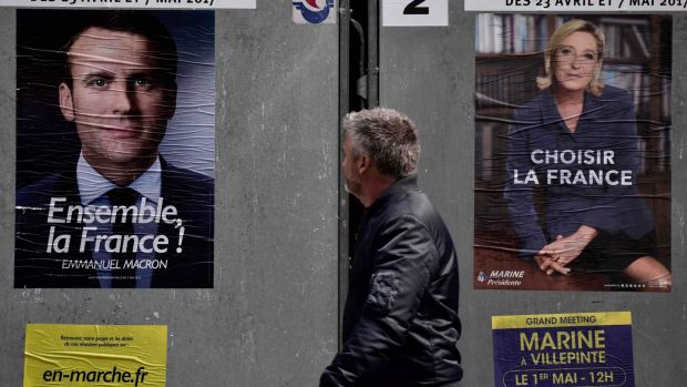 A pedestrian walks past posters of French presidential election candidate for the En Marche! movement Emmanuel Macron and far-right candidate Marine Le Pen, in Paris. Photograph: Philippe Lopez/AFP/Getty Images
