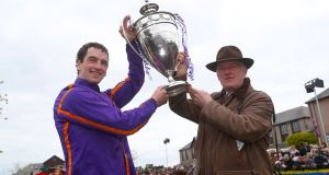 Patrick Mullins and his father, trainer Willie Mullins,   lift the cup in the parade ring after winning the Betdaq Punchestown Champion Hurdle with Wicklow Brave at Punchestown Festival. Photograph: Brian Lawless/PA Wire