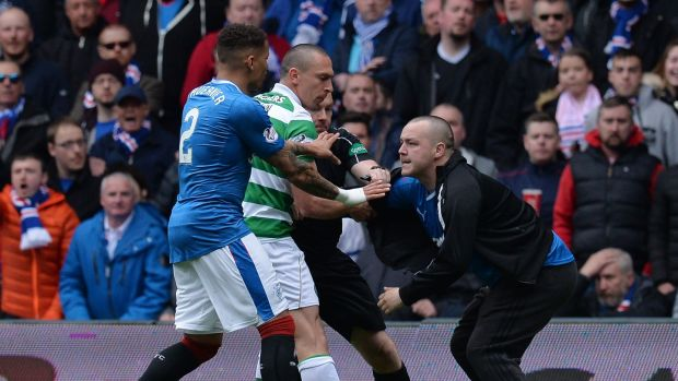 A pitch invader comes on to the pitch and approaches Celtic captain Scott Brown. Photograph: Mark Runnacles/Getty Images