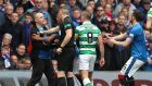 A Rangers fan invades the pitch as Celtic's Scott Brown looks on. Photograph: Reuters