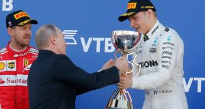 Russian president Vladimir Putin hands over the trophy to Valtteri Bottas. Photograph: Reuters