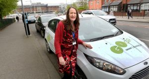 Joan Scales with a GoCar.  The cars are a variety of Ford and Hyundai superminis and hatchbacks, and also a few  BMW i3 electric cars. Photograph: Cyril Byrne