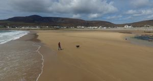 A woman and her dog enjoy the restored beach at Dooagh on Achill Island. Photograph: Sean Molloy