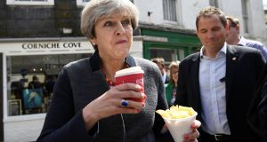 Britain's prime minister Theresa May eating chips during a campaign stop in Mevagissey, Cornwall, on Tuesday. Photograph:  Dylan Martinez/WPA Pool/Getty Images