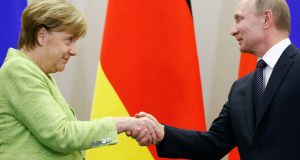 Russian president Vladimir Putin and German chancellor Angela Merkel shake hands during a joint news conference following their talks in Sochi on Tuesday. Photograph:  Alexander Zemlianichenko/Reuters