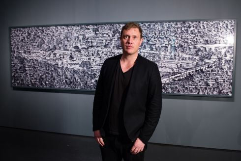 Richard Mosse pictured with his work. Mosse was born in Ireland in 1980 and received his MFA in Photography from Yale University in 2008. His work has been exhibited in major museums and galleries worldwide. His latest series, Heat Maps, was exhibited at the Barbican, London, in February 2017. Photograph: Jeff Spicer/Getty Images for Prix Pictet