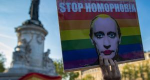 "A demonstrator holds a placard depicting Russian president Vladimir Putin with the label ""Stop Homophobia"", to denounce a homophobic campaign  in  Russia-sponsored  Chechnya, during a protest held on Place de la Republique in Paris, France, late in April. File photograph: Ian Langsdon/EPA"