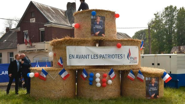 The banner under the photograph of Marine Le Pen in Ennemain reads, 'Forward the Patriots'.