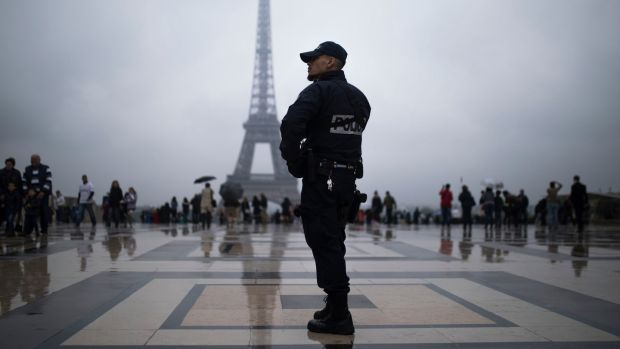 A French police officer patrols at Trocadero plaza with the Eiffel Tower in the background in Paris.