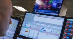 A television screen displays news footage relating to the result of France's presidential election, as traders works on the trading floor of ETX Capital in London on May 8th. Photograph: Chris Ratcliffe/AFP/Getty Images