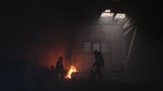 Migrants stand by a fire inside a derelict customs warehouse in Belgrade, Serbia. Photograph: Marko Djurica/Reuters