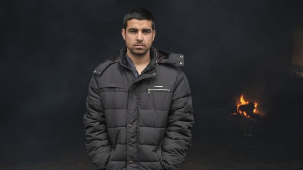Migrant Jamshid Shadab at the entrance of a derelict customs warehouse in Belgrade, Serbia. Photograph: Marko Djurica/Reuters