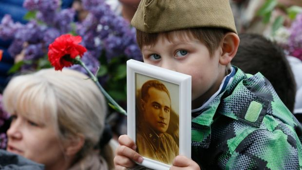 A Ukrainian boy carries a portrait of a relative at Victory Day celebrations in Kiev, Ukraine. Photograph: Sergey Dolzhenko/EPA