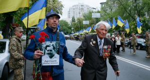 A Ukrainian man carries a portrait of a relative and helps a veteran before a march for Victory Day celebrations in Kiev, Ukraine. Photograph: Sergey Dolzhenko/EPA