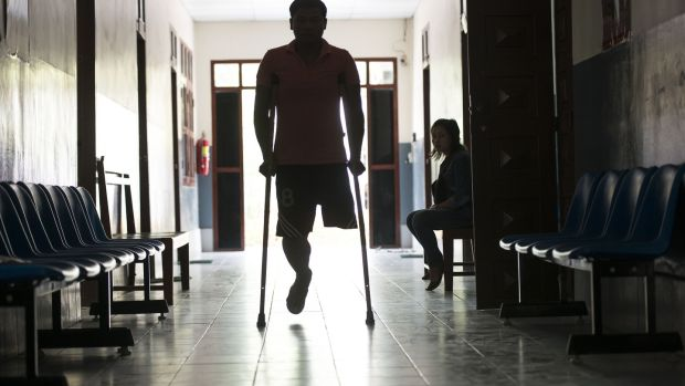 A man arrives at the Cope centre in Vientiane, Laos. Cope was formed in 1997 in response to the need to provide UXO (unexploded ordnance) survivors with care and support, and orthotic and prosthetic devices which are made on site at the centre. Photograph: Brenda Fitzsimons