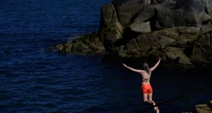 A woman jumps into the sea at the Forty Foot diving area in Sandycove, Dublin, on Wednesday. Photograph: Clodagh Kilcoyne/Reuters
